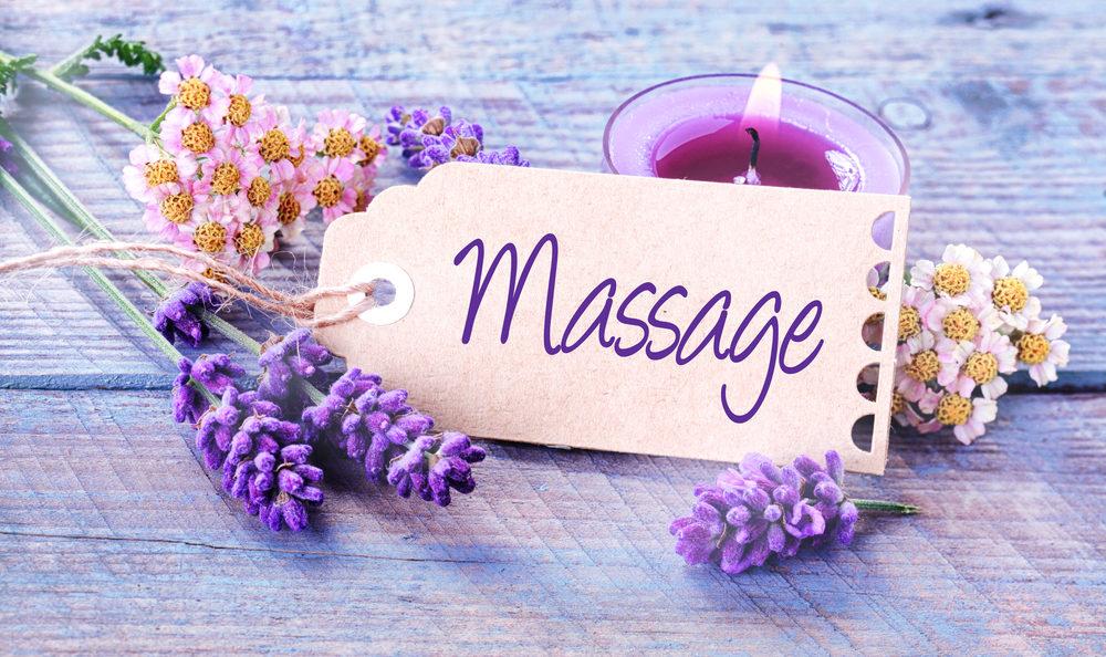 Massage kaartje ligt tussen lavendel en witte en roze bloemen met op de achtergrond een kaars.