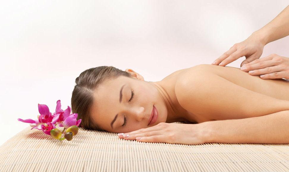 Vrouw ligt op een massage tafel en wordt energetisch gemasseerd.